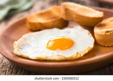 One fresh fried egg sunny side up with toasted baguette slices on the side served on wooden plate (Selective Focus, Focus on the front of the egg yolk)