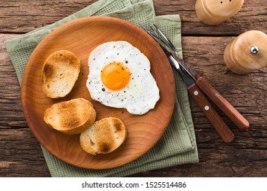 One fresh fried egg sunny side up with toasted baguette slices on the side served on wooden plate, photographed overhead (Selective Focus, Focus on the egg)
