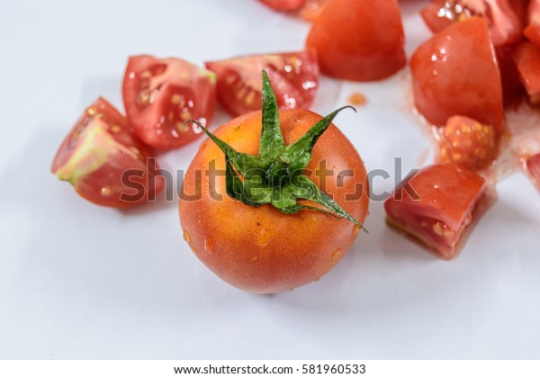 one fresh full  tomato with blurry sliced tomatoes.