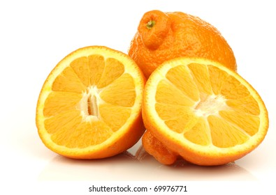 one fresh minneola and a cut one on a white background