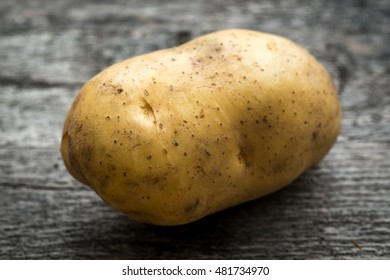 One Fresh Potato on Wood Table Background. close up