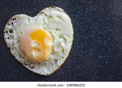 One fried egg on a dark background. Heart shape. Good morning darling! A good start to the day. Simple home kitchen. Daylight.