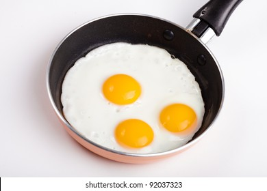 One fried egg on a pan without oil isolated on white
