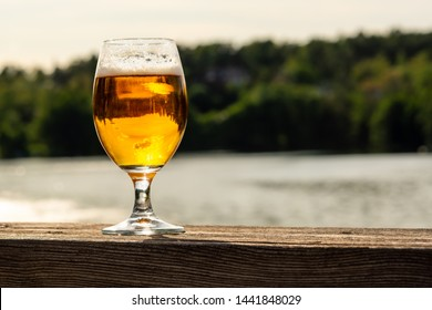 One full glass of beer against sea and nature background. Landscape reflection in the glass.