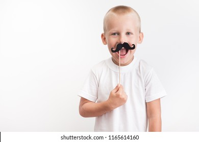 One funny boy in a white T-shirt holding photo booth mustache on background. holiday concept of father day. joyful kid.
