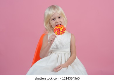 One giant whirly pop can last a very long time. Happy childhood food. Small girl hold lollipop on stick. Small child with sweet lollipop. Happy candy girl.
