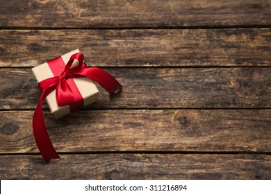 One gift box with an red big ribbon on old wooden dark brown background for christmas.