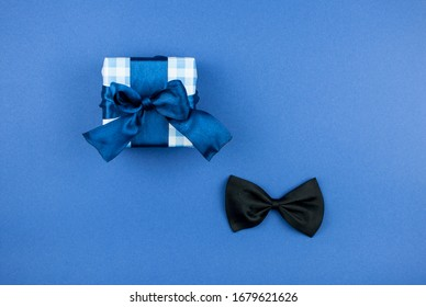 One gift box wrapped in craft paper and tied with bow on dark blue paper background. Concept Father's Day or Birthday background. Top view. International men's day concept.