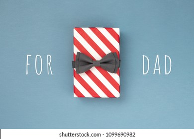 One gift box wrapped in red striped paper and tied with the grey bow tie on blue-gray background. The idea of gift design for a DAD. Holiday concept.