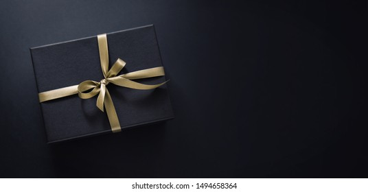 One gift wrapped in dark black paper with luxury bow on dark background. Horizontal with copy space. Banner