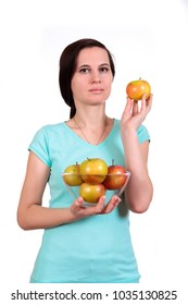 One girl holds in hand a glass vase with apples, in other hand apple about the person, on the isolated white background