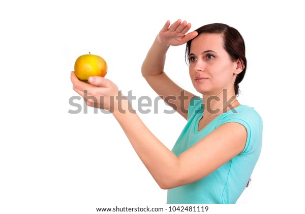 One girl in a t-shirt holds before herself apple in hand, other hand is bent over the head, looks forward afar, on the isolated white background