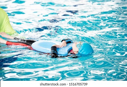 One girl wearing a swimsuit uses a foam pad to practice swimming in a swimming pool with a teacher. She happily and smiling.