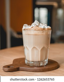 One glass of hot coffee with marshmallow on top serve on wood tray on wood table next to bright window in morning. Selective focus.