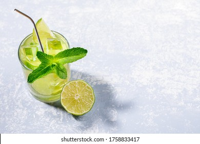 One glass with iced green matcha tea with lime, ice, fresh mint and metal drinking straw on light grey backdrop with trendy shadows. Healthy food, No Plastic, Zero Waste concepts. Copy space for text.