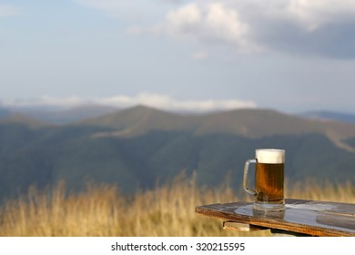 One glass mug with lager or porter tasty frothy beer on wooden table top sunny day outdoor on natural with mountain hills and yellow dry grass and cloudy sky background copyspace, horizontal picture