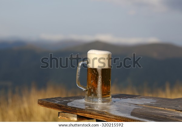 One glass mug with lager or porter tasty frothy beer on wooden table top sunny day outdoor on natural with mountain hills and yellow dry grass background, horizontal picture