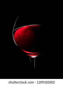 One Glass of Red Wine photographed with rim light against black background (focus on edge of glass)