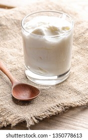 One glass of yogurt and wooden spoon on burlap napkin on wooden table.