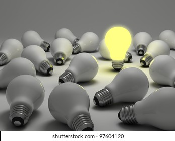 One glowing light bulb amongst the unlit incandescent bulbs on white background