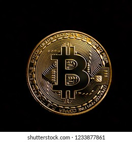 one gold Bitcoin on black