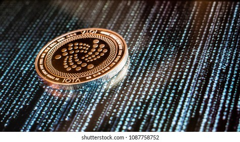 One golden Iota coin on a background of black and blue computer and binary code.