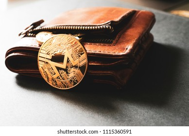 One golden Monero coin leaning against an open leather wallet on a plain surface