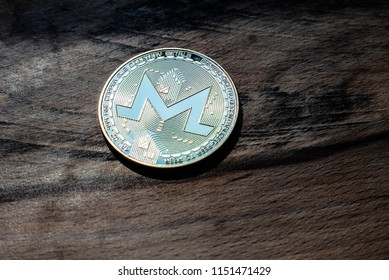 One golden Monero coin on a background of grained wood.
