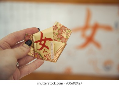 "One golden o-mikuji (random Japanese fortune telling written on strips of paper), for women, from Gokoku Jinja, Shinto Shrine, Sendai, Japan. The Japanese text means ""woman fortune telling"""