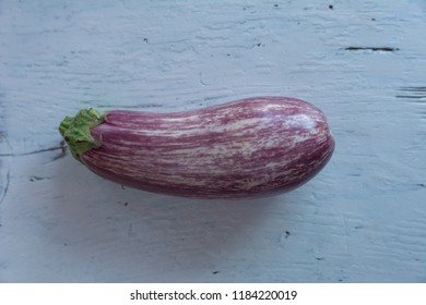 One graffitti eggplant on white rustic wooden background
