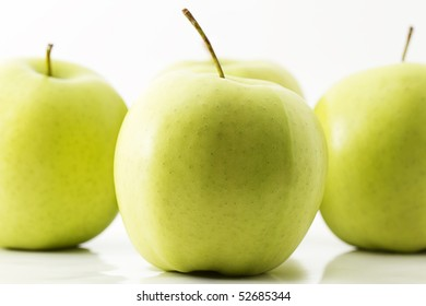 one green apple in front of three green apples on white background