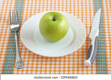 One green Apple is in a glass white plate on an orange tablecloth in indoor. The concept of diet and healthy food.