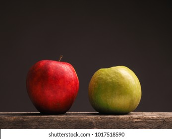 One green apple and one red apple on a rustic wooden table with place for text