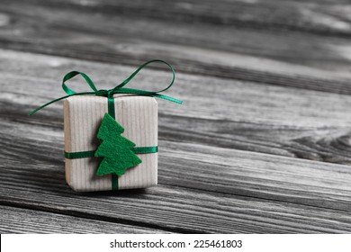 One green christmas present on wooden grey background.