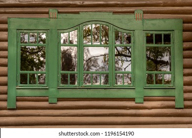 One green window with reflections on brown timber exterior building wall. Decorative traditional wooden frame.