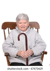one grey haired senior adult woman sitting in a rocking chair holding a wooden cane isolated over white