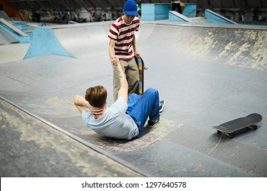 One of guys helping his fallen friend to stand up during incident at parkour area or lesure center