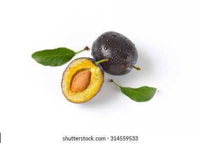 one and half washed plums on white background