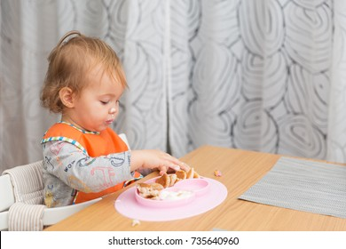 One and a half year old baby girl feeding herself with her fingers, baby led weaning; concept of motherhood and parenting