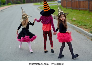 One of halloween girls looking back while going to play tricks with friends