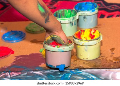 One child´s hand is getting some acrylic colors from a plastic can. Getting hands full of color. The main objective is to have fun and get dirty been creative. In picture one can see one hand.