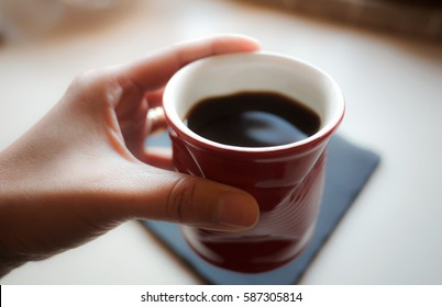 One hand holding red cup of coffee, mug of hot drink in the morning