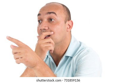 One hand is over the mouth and the other is pointing to the side. Man is surprised and watches closely.