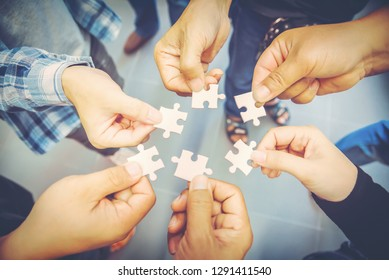 one hand trying to connect puzzle piece . Jigsaw alone wooden puzzle against sun rays. one part of the whole. business strategy