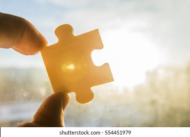 one hand trying to connect puzzle piece with sunset background. Jigsaw alone wooden puzzle against sun rays. one part of the whole. symbol of association and connection. business strategy. copy space