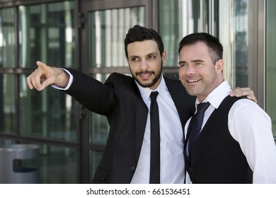 one handsome businessman is showing another something by pointing
