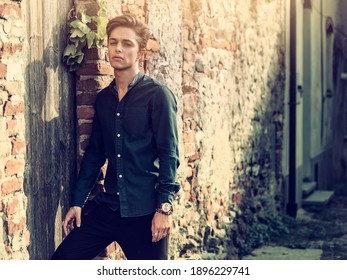 One handsome elegant young man in urban setting in European city, standing in sunny day, looking at camera