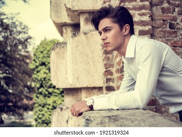 One handsome elegant young man in urban setting in European city, standing in sunny day