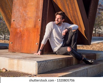 One handsome man in city setting sitting by rusty metal structure in European city, looking away