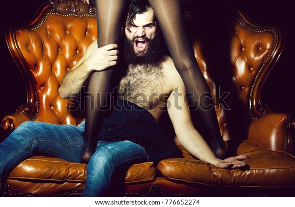One handsome serious young adult man with long black lush beautiful beard moustache and bare hairy chest sitting on leather couch with sexy female legs in stockings indoor, horizontal picture